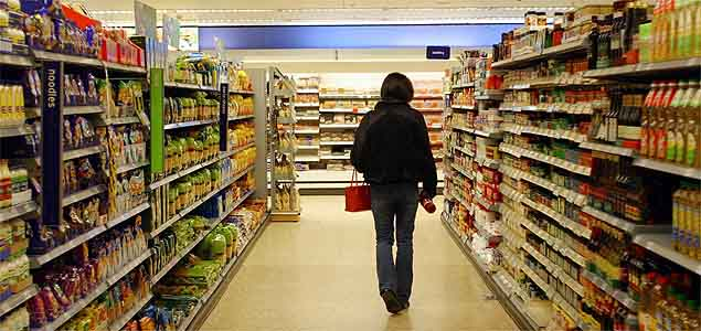 A customer browses goods in an aisle at  the Sainsbury store in west London, Wednesday, April 7, 2004. Britain's third-largest supermarket chain, reported its first-ever net loss after Chief Executive Justin King began a restructuring costing 550 million-pounds ($1 billion) to regain market share.  Photographer: Graham Barclay/Bloomberg News