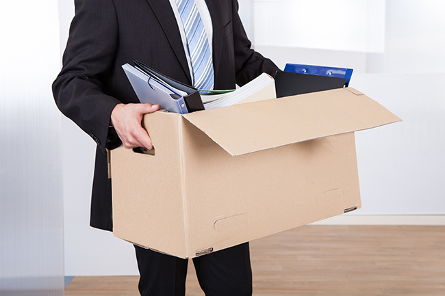 Midsection of businessman moving out with cardboard box from office