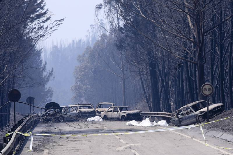 Pedrogao Grande (Portugal), 18/06/2017.- Burnt cars and body bags on the N236 road between Figueiro dos Vinhos and Castanheira de Pera, near Pedrogao Grande, central Portugal, 18 June 2017. At least fifty-seven people have been killed in forest fires in central Portugal, with many being trapped in their cars as flames swept over a road on the evening of 17 June 2017. A total of 688 firefighters are providing assistance. (Incendio) EFE/EPA/MIGUEL A. LOPES